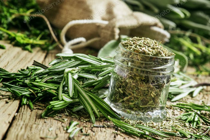 Dried rosemary in a glass jar, branches of fresh rosemary