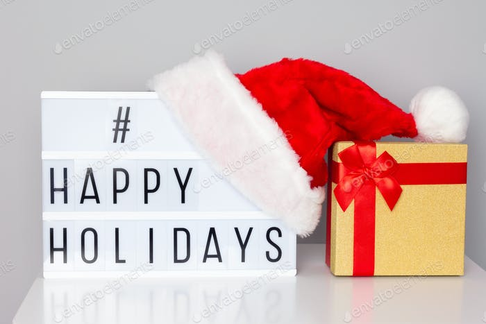 Lightbox with happy holidays hashtag text, Santa hat and gift box