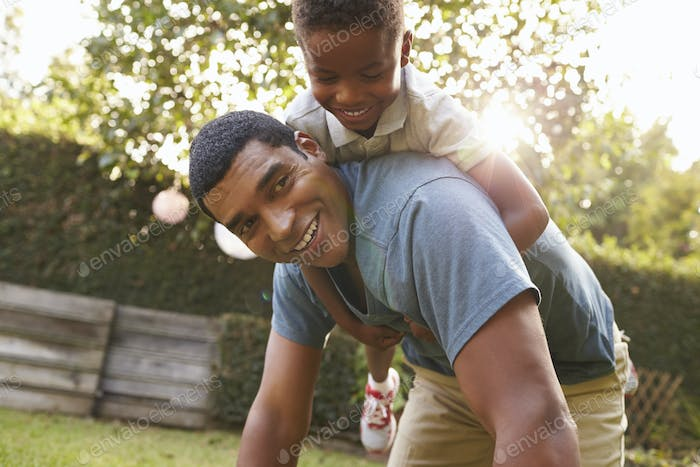 Young black boy playing on dad's back in a garden, low angle