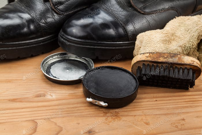 Shoe polish with brush, cloth and worn boots on wooden platform