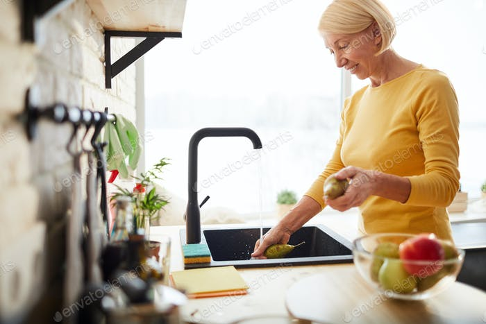 Happy woman cleaning fruits