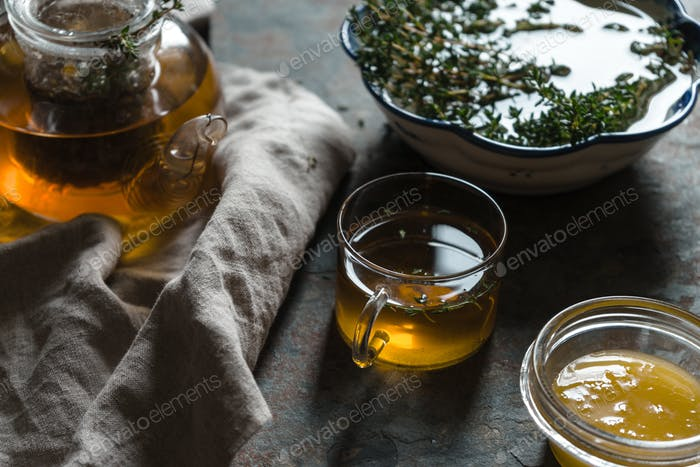 Kettle with green tea, thyme and honey on the table