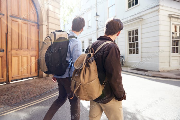 Rear View Of Male Gay Couple On Vacation Wearing Backpacks Walking Along City Street