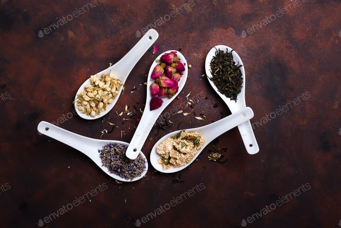 Herbal natural floral tea infusion with dry flowers lavender on clay spoons on stone background