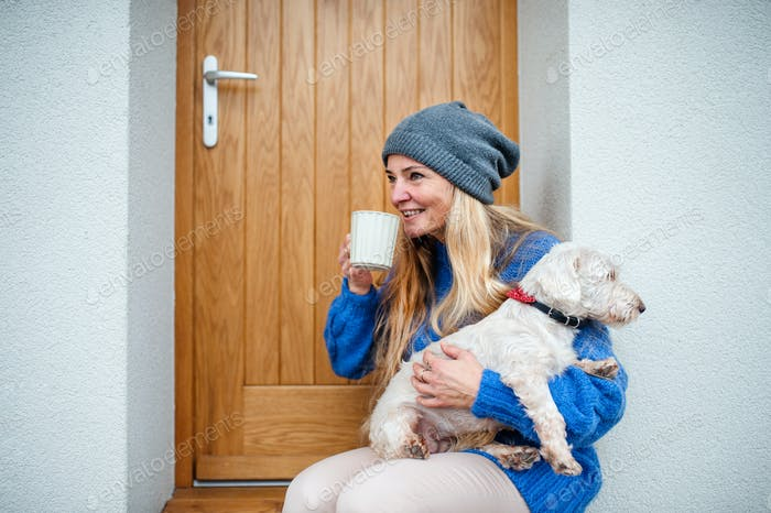Mature woman relaxing outdoors by front door at home with coffee and pet dog