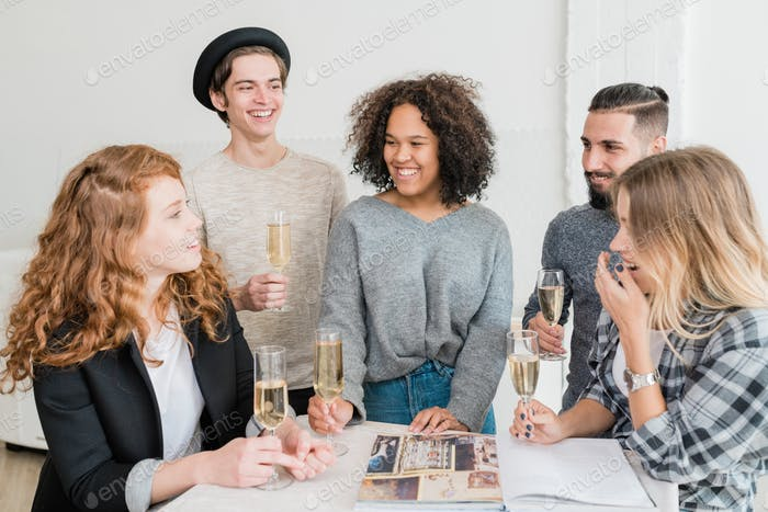 Laughing friends with champagne looking at one of girls telling funny stuff