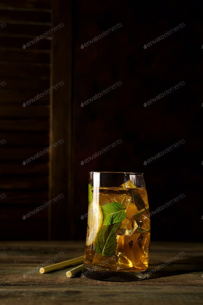 cocktail glass with ice, mint and ginger on a dark wooden backgorund