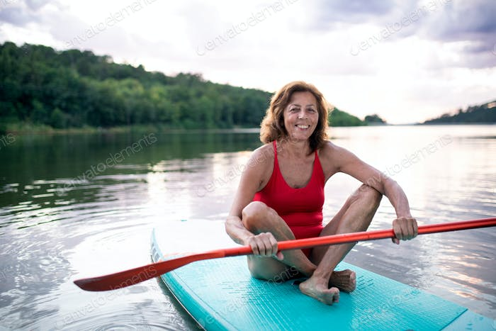 Senior woman paddleboarding on lake in summer. Copy space