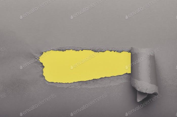 Grau zerrissenes Papier mit gelbem Papier auf Hintergrund