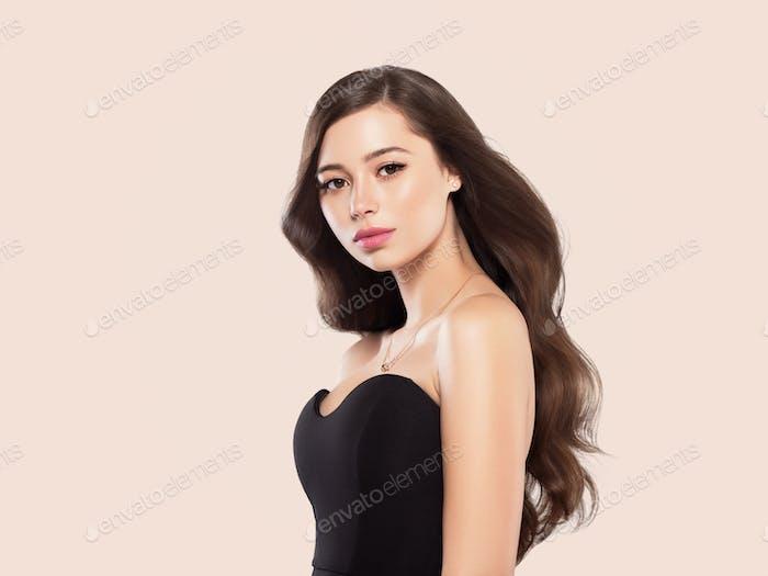 Beautiful woman hair long brunette healthy hairstyle beauty makeup. Beige background.