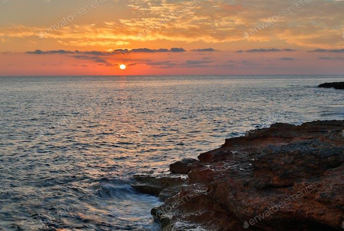 setting sun over the sea and rocks