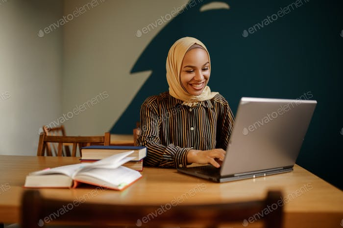 Arab female student in hijab using laptop in cafe