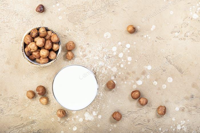 Vegan Hazelnut nut milk in bottles, closeup, beige table