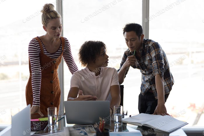 Front view of multi-ethnic business colleagues discussing over laptop in modern office