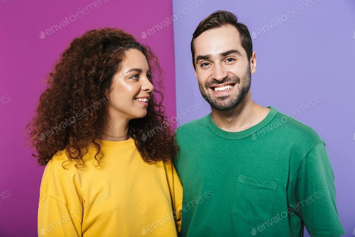 Portrait of cheerful caucasian couple in colorful clothing smiling together, woman looking at man