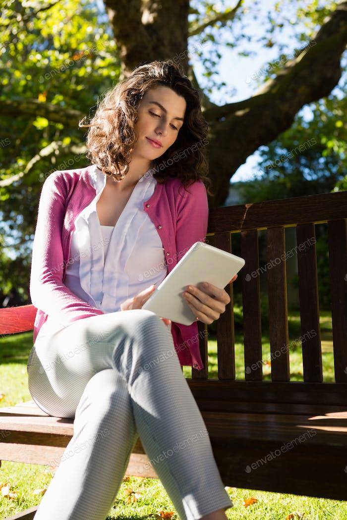 Frau sitzt auf der Bank und mit digitalem Tablet im Garten