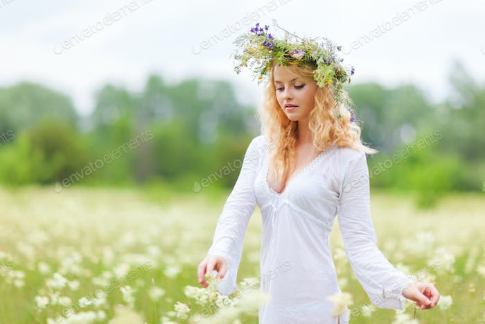 Young beautiful blond woman in white dress and floral wreath standing and looking at camera on