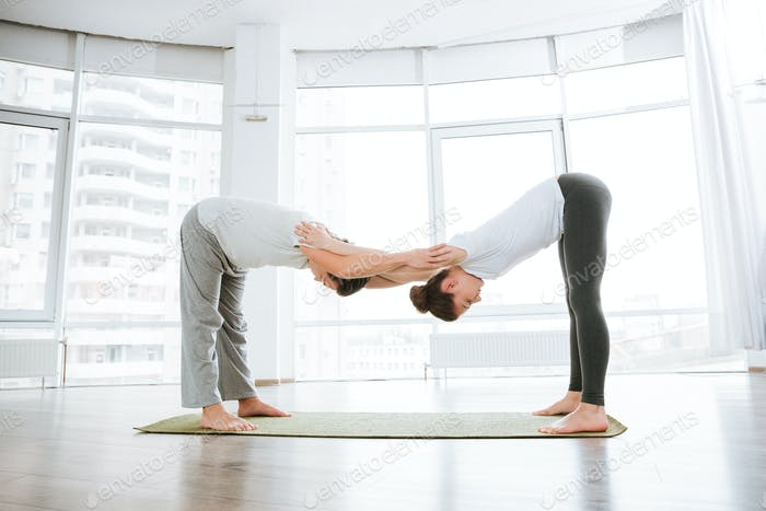 Young couple doing flexibility workout in yoga studio together