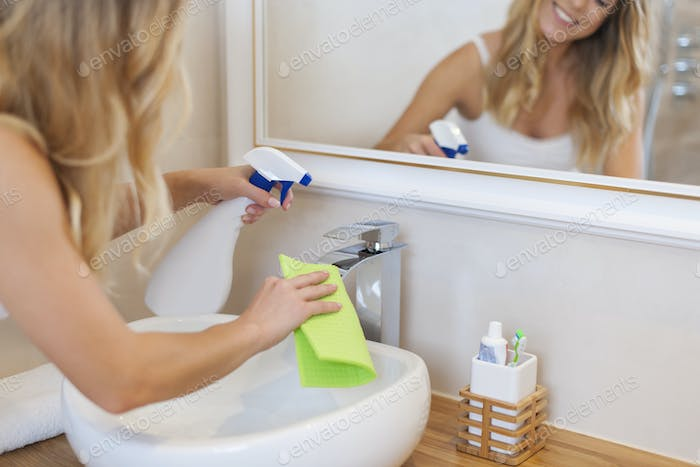 Blonde young woman cleaning bathroom