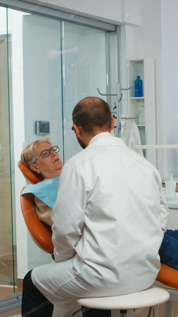 Dental specialist talking with senior patient