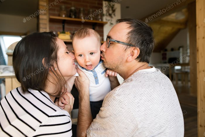 Beautiful young parents kissing their cute baby son