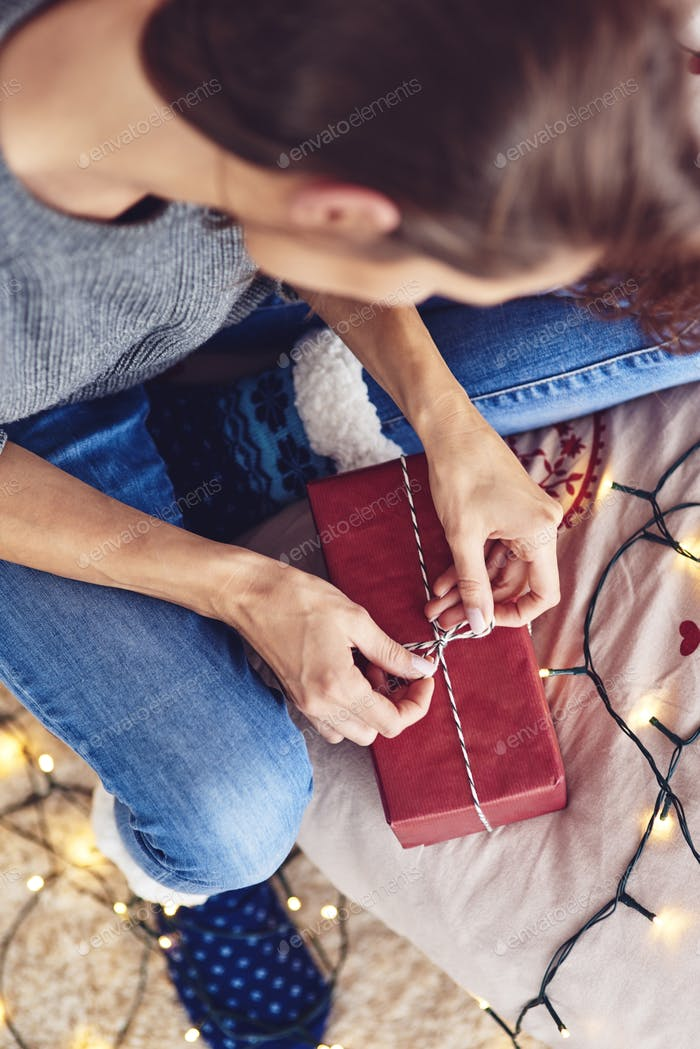 Young woman packaging holiday gift