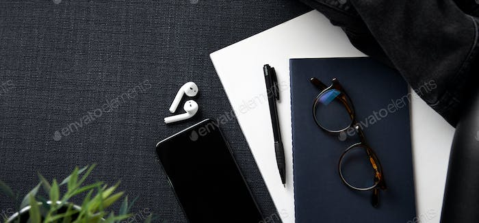 Flat Lay Lifestyle Shot With Jacket Notebook Mobile Phone And Wireless Earphones On Black Background