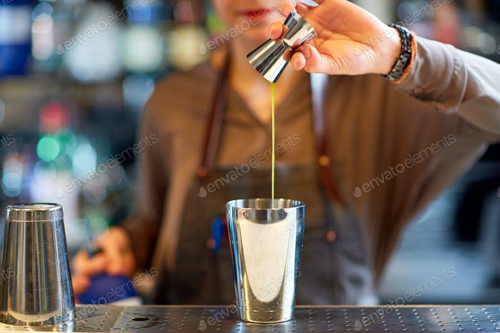 bartender with cocktail shaker and jigger at bar