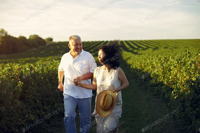 Beautiful adult couple spend time in a summer field