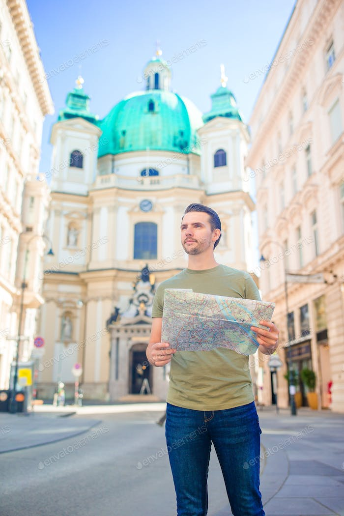 Man tourist with a city map and backpack in Europe street. Caucasian boy looking with map of