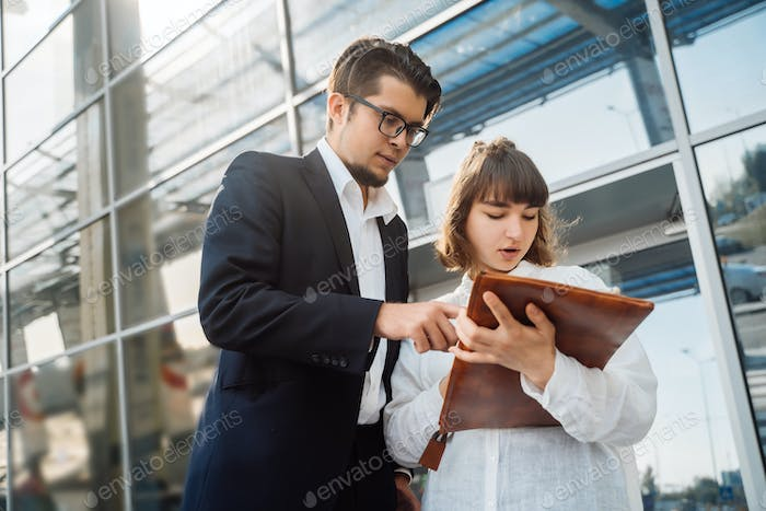 Businessman and businesswoman look at important papers