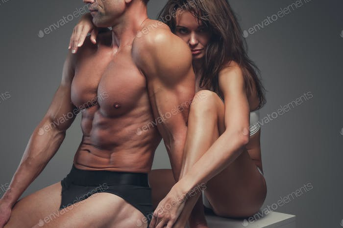 Fitness couple posing in a studio.