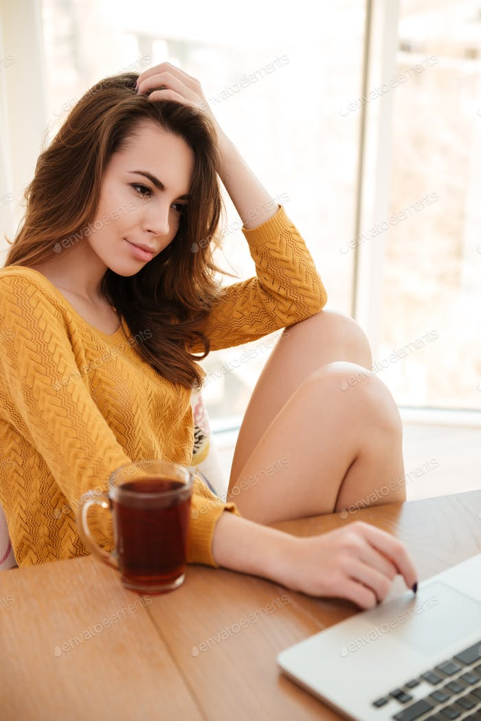 Young attractive woman in sweater working with laptop at home