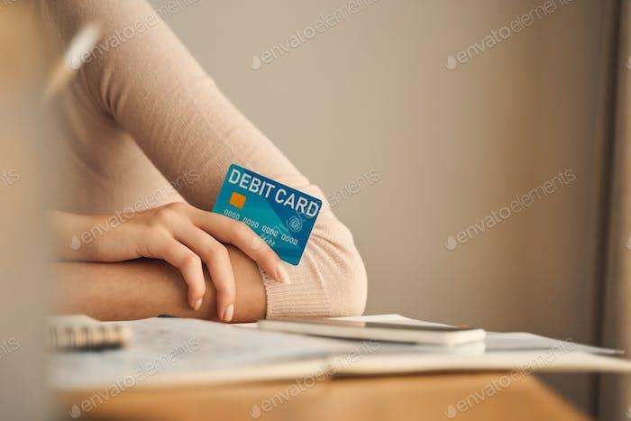Woman in a sweater holding a debit card