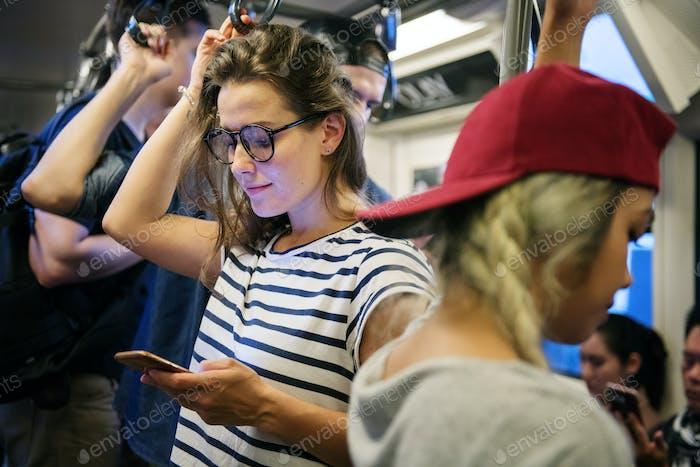Junge Frau mit einem Smartphone in der U-Bahn