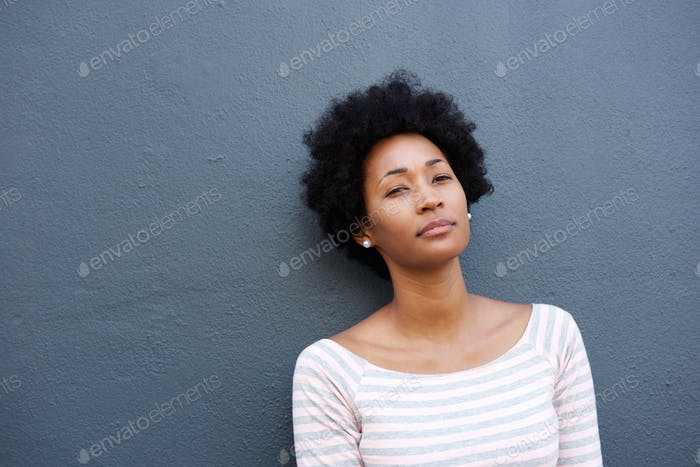 Serious woman standing alone against gray wall