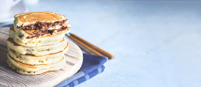 Stack of Stuffed chocolate nutella pancakes on wooden board on blue background. American Breakfast