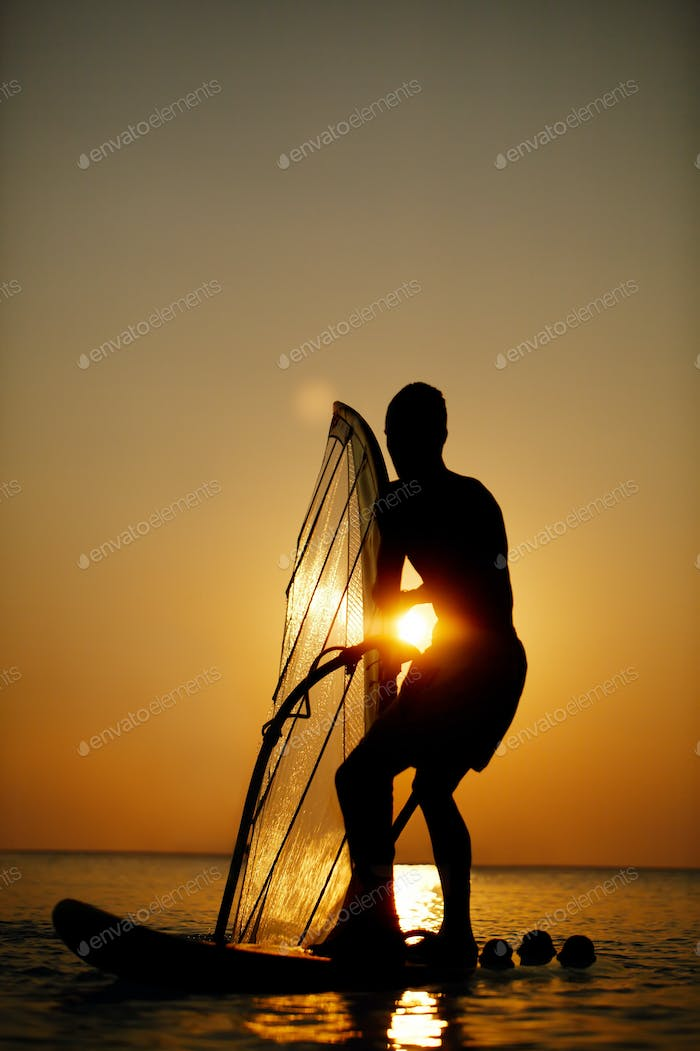Man sailboarding at sunset