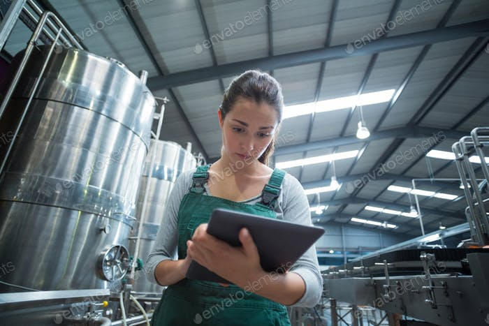 Weibliche Fabrikarbeiter pflegen Rekord auf Zwischenablage in der Fabrik