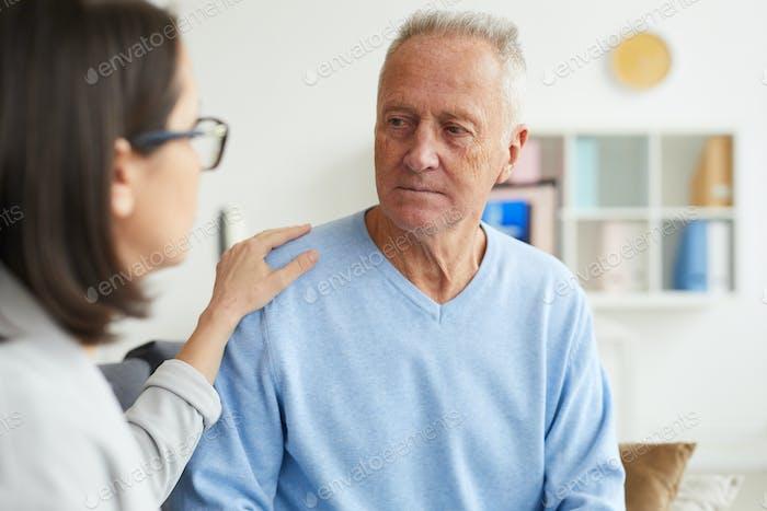 Senior Man Listening to female Doctor in Clinic