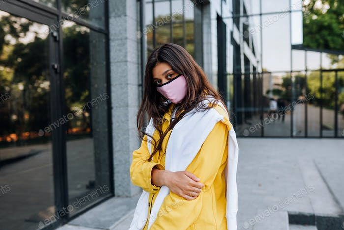 Young woman wearing mask posing on street