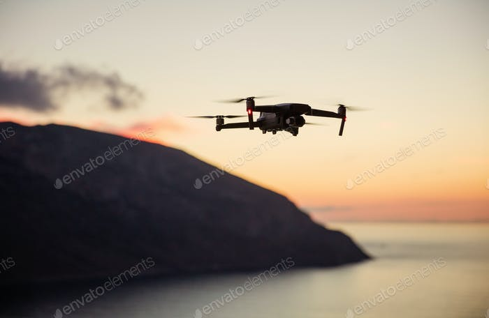 Drone quadcopter with digital camera flying over coast at sunset