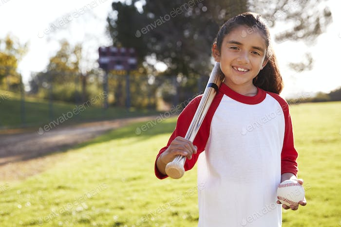 Young Hispanic girl with baseball and bat smiling to camera