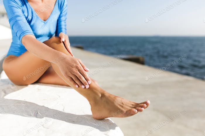 Nahaufnahme Foto von Frau Körper sitzt auf weißem Stein mit schönem Meerblick auf Hintergrund