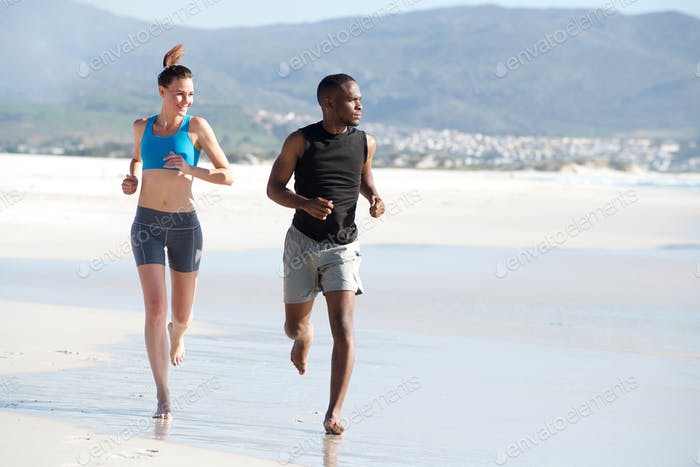 Healthy young couple running along the beach