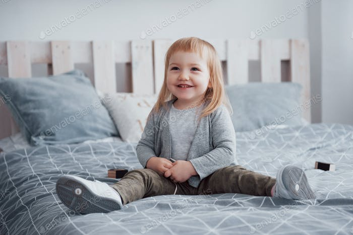 glückliches kleines Mädchen mit einem Kissen im Bett zu Hause