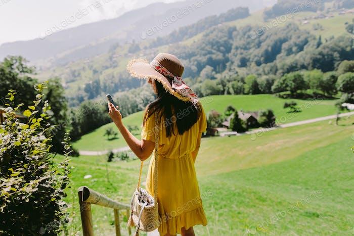 Frau mit Smartphone auf Sommerferien ländlichen Dorf in Europa