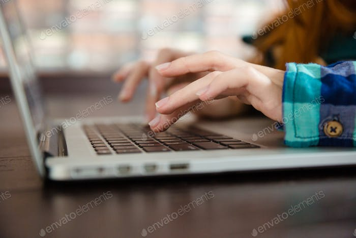 Hands of young woman typing using laptop