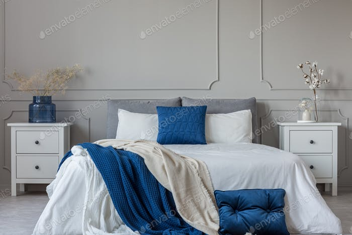 King size bed with grey, blue and white bedding between two wood