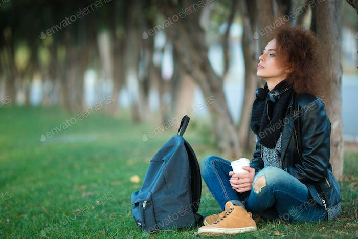 Female student sitting on green grass with cup of coffee